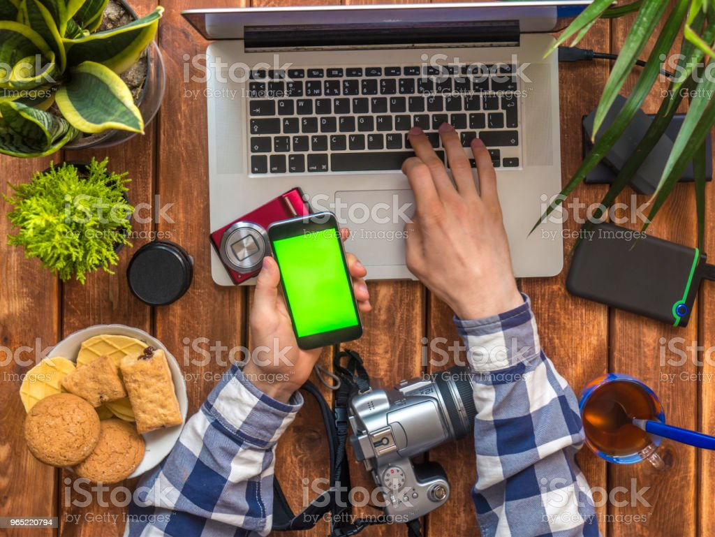 person's hands holding smartphone with chroma key and working at new photoes zbiór zdjęć royalty-free