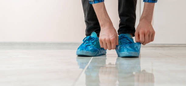 person's hands put on the blue shoe covers on the dirty sneakers in the hospital stock photo