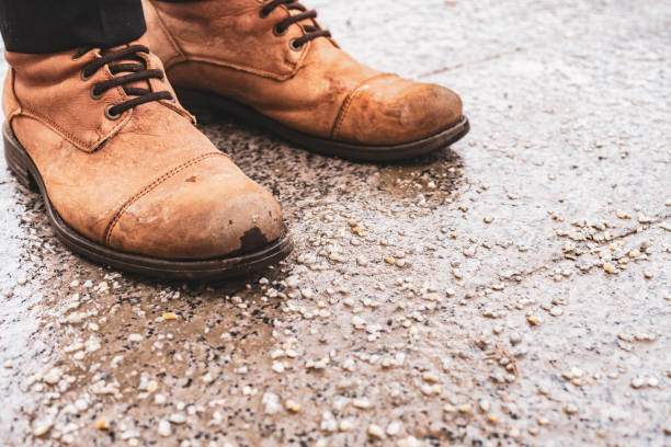 persons shoes on salted pavement in the city stock photo