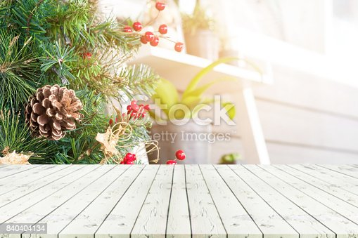 istock Perspective empty wooden table in front ofchristmas tree and blur decoration at coffee shop background, for product display montage or design layout. 840404134