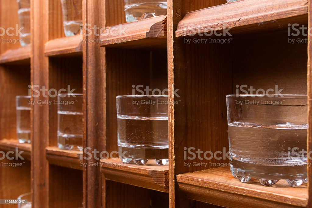perspective from wooden shelves with glasses for alcohol, shots on...