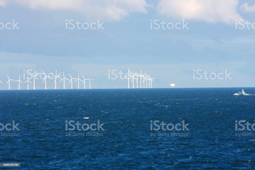 Perspective Line Of Ocean Wind Mills With Dark Water Stock Photo