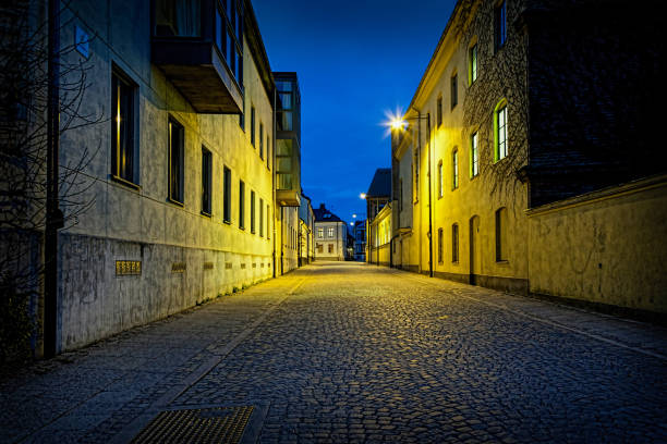 perspective night view of a empty urban cobblestone street with moody lights in lund, sweden. tranquil feeling of silence. - lund stock photos and pictures