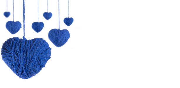 Perspective of hearts made of blue wool yarn on a white background stock photo