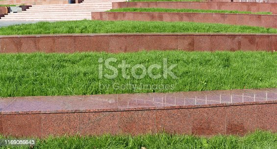 Perspective of steps made of red granite stone and fresh green grass. Panoramic outdoor background