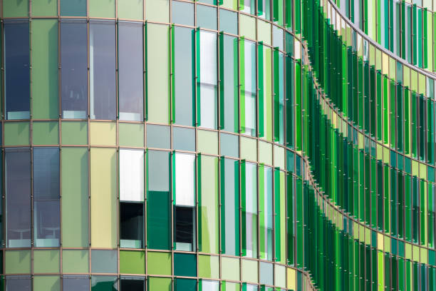 Perspective of the facade of a modern office building with cool green glass panels stock photo