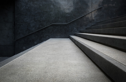 Perspective of the staircase and railing on concrete or marble walls.