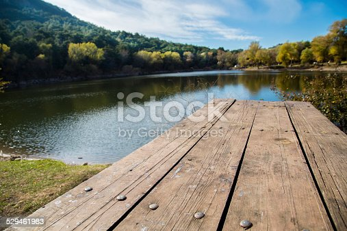 989111446istockphoto Perspective of wooden picnic table with blur landscape background 529461983