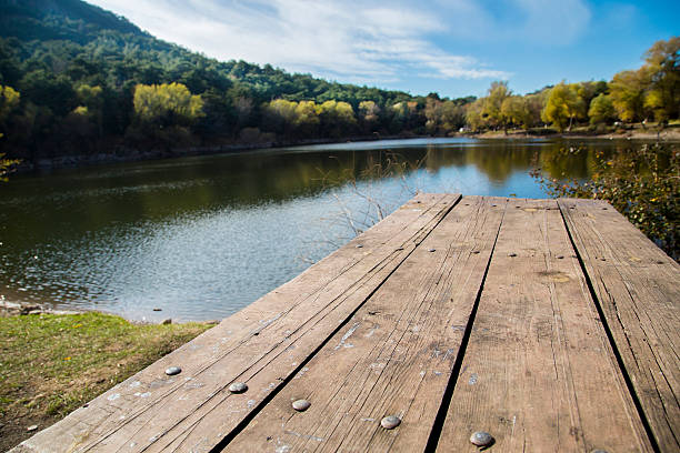 Perspective of wooden picnic table with blur landscape background stock photo