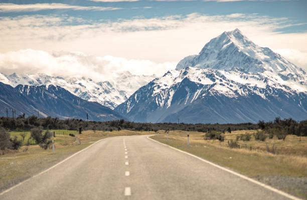 perspektive weg zur bergkette im bewölkten tag herbstsaison schnee in neuseeland - neue abenteuer stock-fotos und bilder