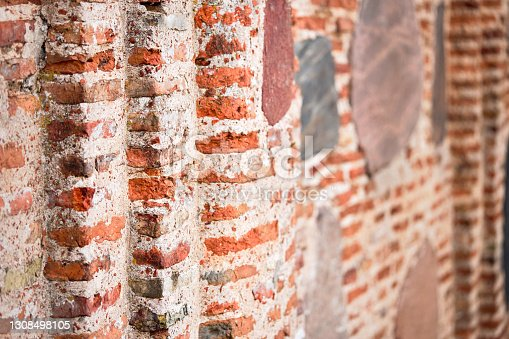 Perspective selective focus red brick wall texture background. Ancient masonry of brick and stone thousand years wall of St Boris and Gleb or Kalozhskaya Church in Europe city Grodno, Hrodna Belarus.