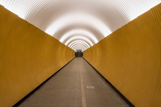 Perspective view of long modern futuristic yellow underground pedestrian tunnel in Stockholm Sweden. stock photo