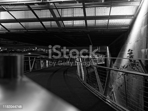 Perspective view of pedestrian overpass above the River Thames with steel fence and guard rails at night. Black and white image. Bridges and the river are seen in the background.