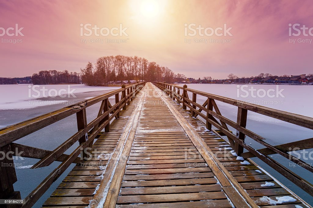 Perspective view of wooden bridge over frozen river stock photo