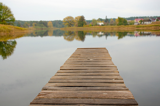 Perspective view of wooden pier at lake. Small bridge in water. Empty wooden bridge or table top with the rural lake and sky landscape. Nature park background and autumn season, product display montage.