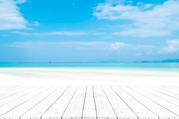 Perspective white pearl wooden table on top over blur sea in sunny day background. Beautiful sea and clouds in Thailand on summer, can be used mock up for montage products display or design layout. stock photo