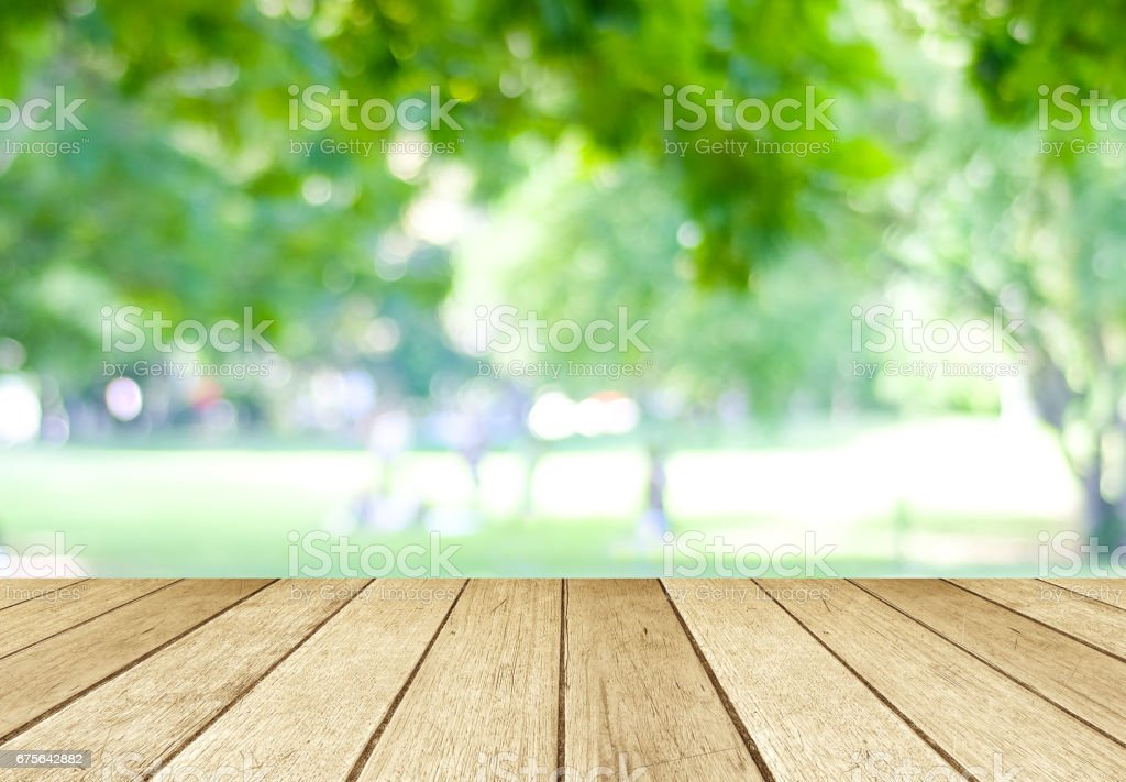 Perspective wood over blur trees with bokeh background, product display montage,  spring and summer season royalty-free stock photo