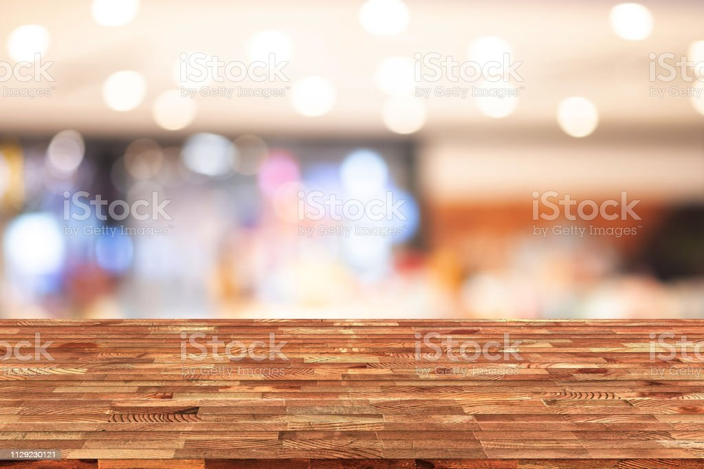Perspective wooden table on top over blur shop background, can be used mock up for montage products display or design layout. stock photo