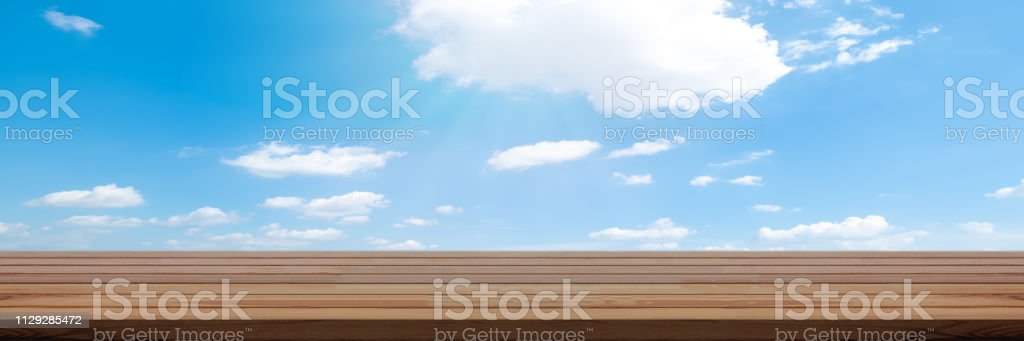 Perspective wooden table on top over blur sky background, can be used...