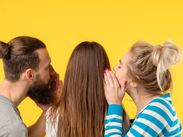 persuasion man woman whisper girls ear Persuasion concept. Man and woman whispering in girls ear. Copy space on yellow background. persuasion stock pictures, royalty-free photos & images