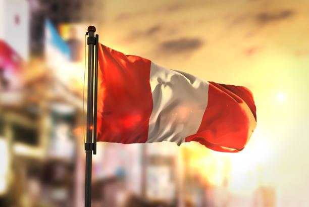 Bandera de Perú contra la ciudad borrosa de fondo en contraluz amanecer - foto de stock