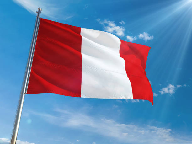 Peru National Flag Waving on pole against sunny blue sky background. High Definition stock photo