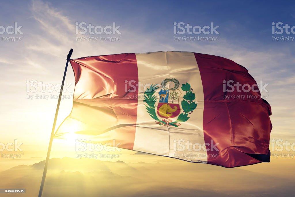 Peru Peruvian flag textile cloth fabric waving on the top sunrise mist fog stock photo