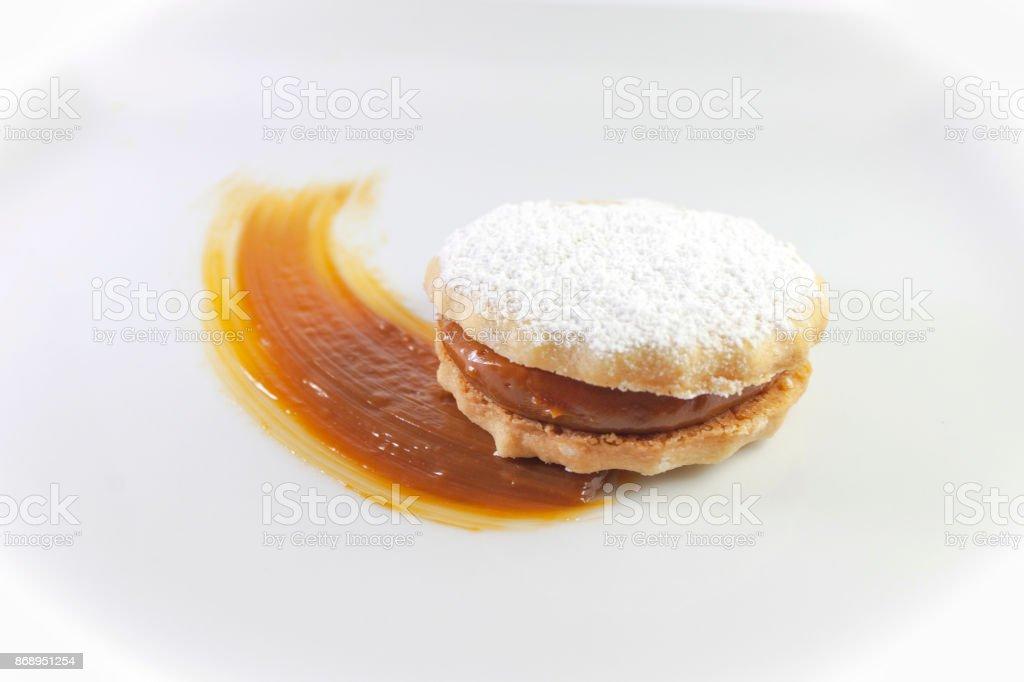Galleta alfajor peruano con azúcar en polvo y caramelo - foto de stock