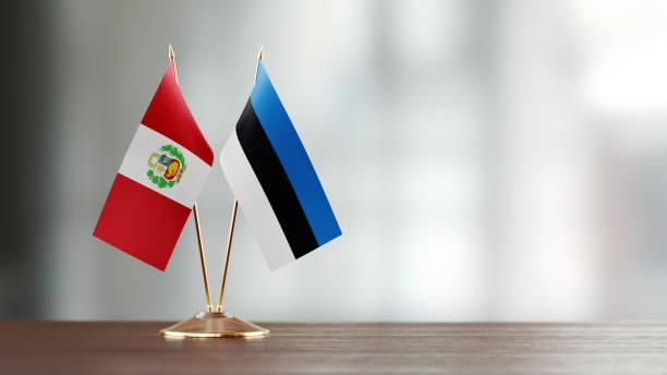 Par de la bandera peruana y Estonia en un escritorio sobre fondo Defocused - foto de stock