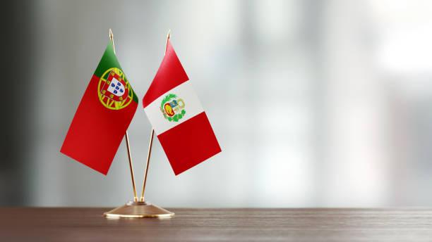 Par de la bandera Portuguesa y peruana en un escritorio sobre fondo Defocused - foto de stock