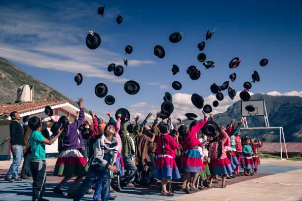 Peruvian children throwing hats to the sky stock photo