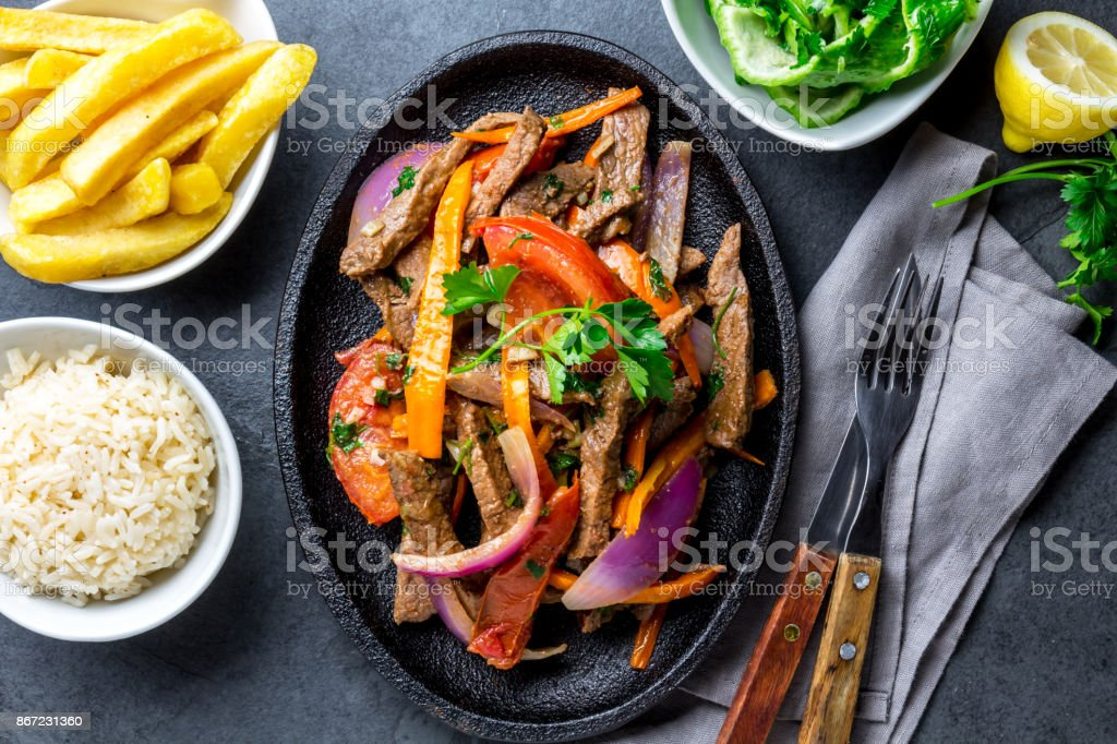 Peruvian dish Lomo saltado - beef tenderloin with purple onion, yellow chili, tomatoes served on black plate, slate background stock photo