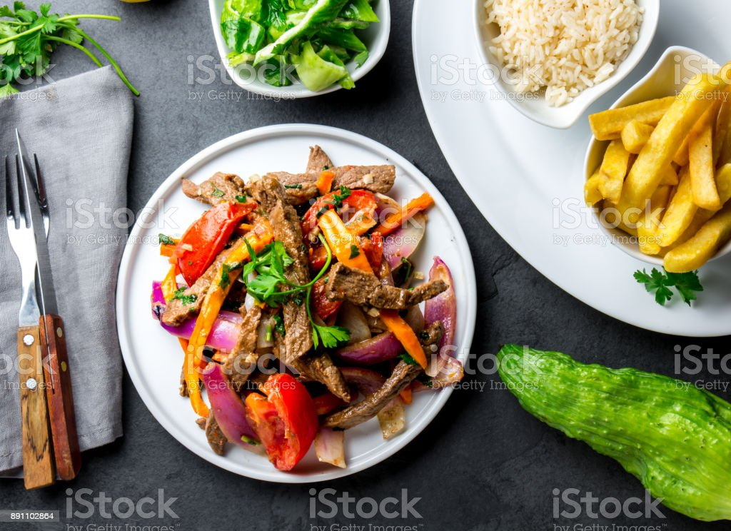 Peruvian dish Lomo saltado - beef tenderloin with purple onion, yellow chili, tomatoes served on white plate, slate background stock photo