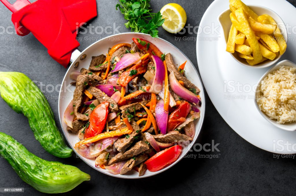 Peruvian dish Lomo saltado - beef tenderloin with purple onion, yellow chili, tomatoes in pan. Tot view stock photo