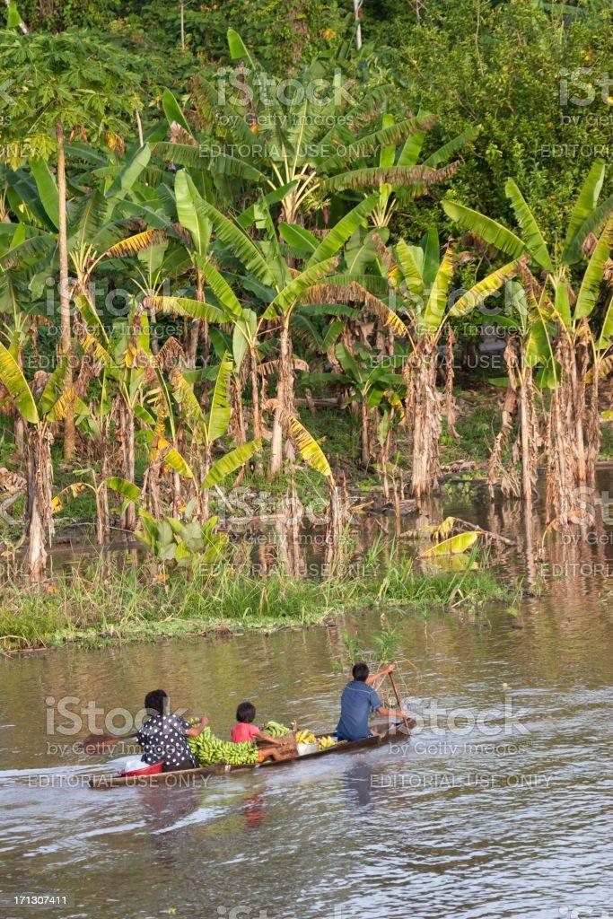 Peruvian family canoeing Amazon River stock photo