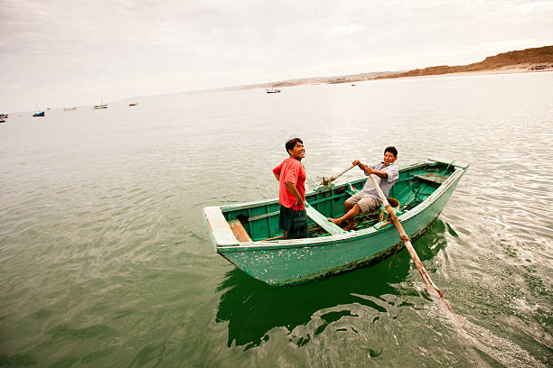 Peruvian fisherman rowing his boat in the morning light stock photo