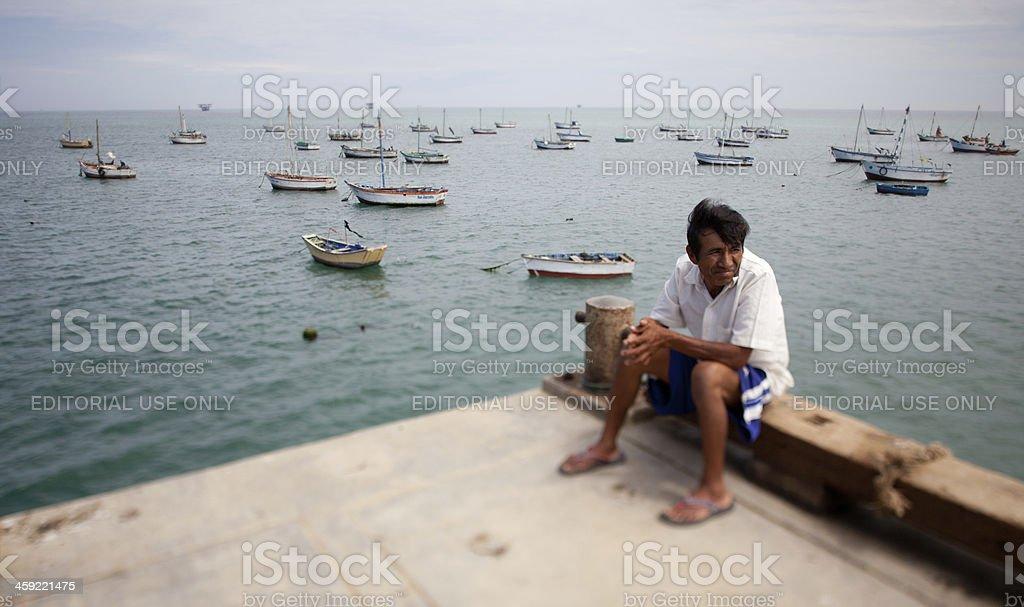 Peruvian Fisherman sitting on the Pier royalty-free stock photo