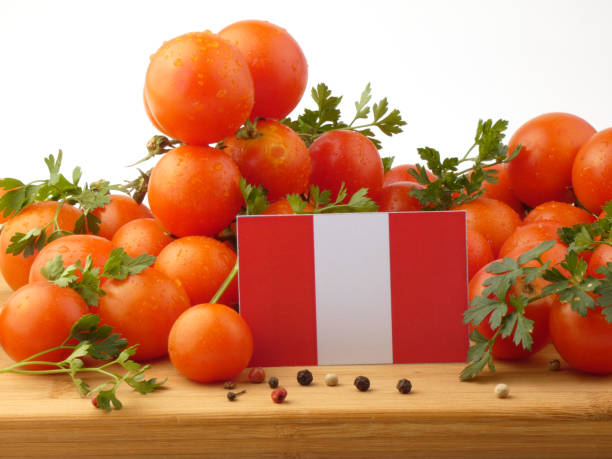 Peruvian flag on a wooden panel with tomatoes isolated on a white background stock photo