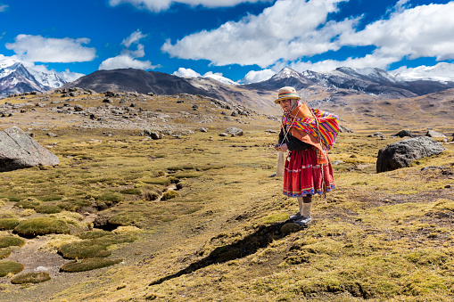 istock Peruvian indigenous old woman standing weaving traditional clothes, Peru. 898712216