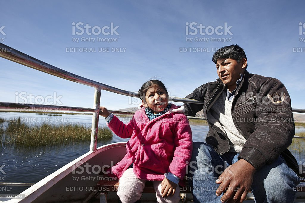 Peruvian man and little girl on boat stock photo