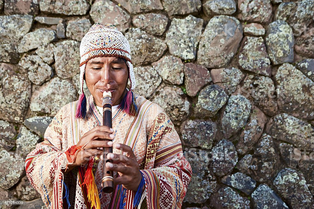 Peruvian man playing flute in front of rock wall stock photo
