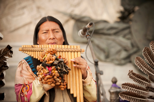 Venice, Italy - March 3, 2014: Peruvian musician with long hair playing on a traditional musical instrument named flute de pan on Piazza San Marco at sea side. The musician wearing wearing national costumes with plume. Venice, Italy.