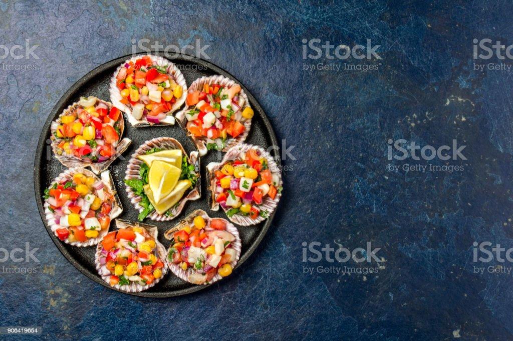 Peruvian style food Scallops a la chalaca. Scallops with onion, tomato, maize, cilantro and lemon on dark blue background. Top view stock photo