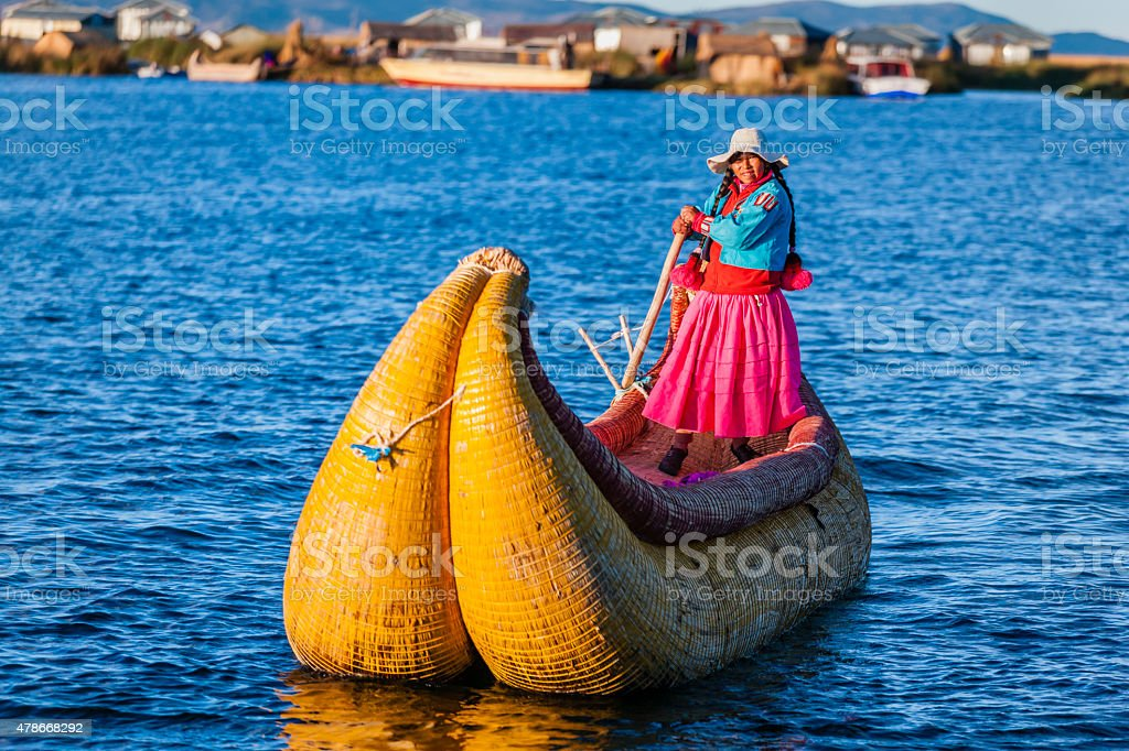 Peruvian woman sailing between Uros floating islands, Lake Tititcaca stock photo