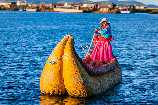 Peruvian woman sailing between Uros floating islands, Lake Tititcaca Peruvian woman sailing between Uros floating islands. Uros are a pre-Incan people that live on forty-two self-fashioned floating island in Lake Titicaca Puno, Peru and Bolivia. They form three main groups: Uru-Chipayas, Uru-Muratos  and the Uru-Iruitos. The latter are still located on the Bolivian side of Lake Titicaca and Desaguadero River. The Uros use bundles of dried totora reeds to make reed boats (balsas mats), and to make the islands themselves. The Uros islands at 3810 meters above sea level are just five kilometers west from Puno port.http://bem.2be.pl/IS/peru_380.jpg peruvian culture stock pictures, royalty-free photos & images