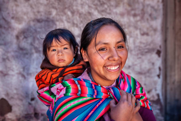 Peruvian woman with her baby on the back in Pisac near Cuzco stock photo