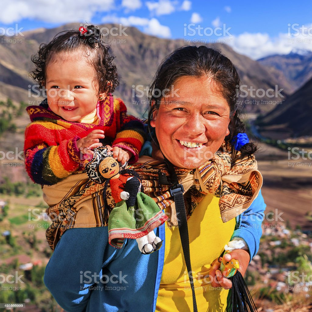 Peruvian woman with her baby on the back near Pisac stock photo