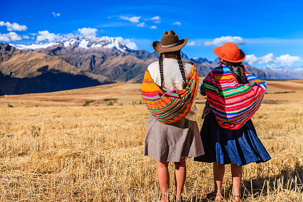 peruvian women in national clothing crossing field, the sacred valley - south america travel stock photos and pictures