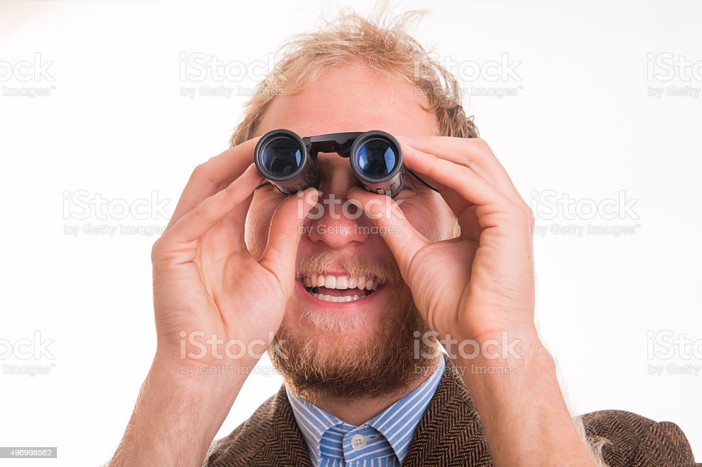 Pervert man watching through binoculars stock photo
