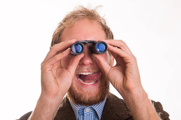Pervert voyeur man watching someone through binoculars stock photo